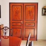 FAUX BOIS : Dans une salle à manger de style Charles X, doubles portes en acajou flammé, avec filet et ornementation en ébène. Ainsi que décor des chaises.