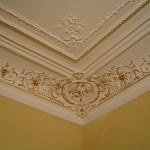 DORURE : Rehauts dorés des motifs ornementés de la corniche d'un salon parisien. (détail)